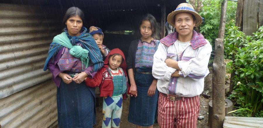 Macario, his wife Santo and three of his children stand outside their home.jpg